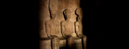 A picture taken on October 22, 2016, shows a ray of light illuminating the statue of Ramses II inside the temple of Abu Simbel in Egypt.  By MOHAMED EL-SHAHED (AFP)