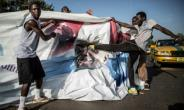 A supporter of the newly elected Gambia President Adama Barrow kicks a poster of the exiting leader Yahya Jammeh in Serekunda.  By MARCO LONGARI (AFP/File)