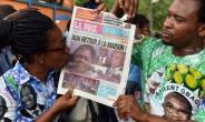 A supporter of Simone Gbagbo kisses a local newspaper bearing the headline