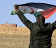 A Saharawi man holds up a Polisario Front flag in the Al-Mahbes area near Moroccan soldiers guarding the wall separating the Polisario controlled Western Sahara from Morocco on February 3, 2017.  By STRINGER (AFP)