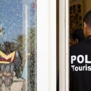 A Tunisian police officer stands guard near a bullet hole at the the Riu Imperial Marhaba Hotel after an attack that left 38 people dead on June 25, 2015.  By KENZO TRIBOUILLARD (AFP/File)