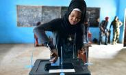 A woman casts her vote in a ballot box at the polling station in Freetown on March 31, 2018 during the second round of Sierra Leone's presidential election.  By ISSOUF SANOGO (AFP/File)