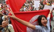 A woman holds the Tunisian national flag during a demonstration in Tunis to demand equal inheritance rights and to mark the country's Women's Day on August 13, 2018.  By FETHI BELAID (AFP)