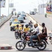 A yellow Benin-Taxi car is seen among several motorbike-taxis at a busy intersection in Cotonou.  By YANICK FOLLY (AFP)