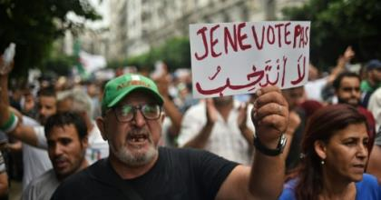 An Algerian protester holds a placard reading