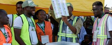 An electoral officer raises a ballot to count results after the Osun State gubernatorial election, which will go to a runoff in what is seen as a litmus test for President Buhari's popularity as he seeks a second term in February.  By PIUS UTOMI EKPEI (AFP)