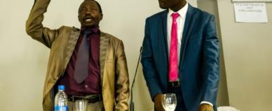 An eyewitness (L) takes an oath before giving his account of events to the head of a commission probing the August 1, 2018 post-poll violence in Zimbabwe which at least six people were shot dead by the military.  By Jekesai NJIKIZANA (AFP)
