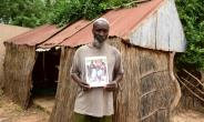 Babacar Ndiaye poses with a photo of his grandfather Abdoulaye Ndiaye, a Senegalese villager who fought for France in World War I.  By SEYLLOU (AFP/File)