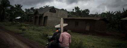 Ebola death: Three people riding a motorbike on a road near Beni carry a cross for a grave.  By John WESSELS (AFP)