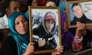 Families of people killed during protests that led to Tunisia's revolution hold photographs of their relatives inside a courthouse in the central city of Kasserine on July 13, 2018.  By HATEM SALHI (AFP)