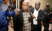 Former Ivory Coast defence chief Moise Lida Kouassi, a key ally of ex-President Laurent Gbagbo, is led away following his arrival in Abidjan in 2012 after being extradited from Togo.  By HO (IVORIAN GOVERNMENT PRESS/AFP/File)