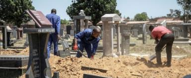 Gravediggers in Johannesburg, where between 45 and 60 graves are re-opened each week on average to allow for second burials.  By GIANLUIGI GUERCIA (AFP)