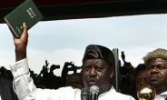 Kenya's opposition leader Raila Odinga (L) holds up a bible as he swears himself in as the 'people's president' in Nairobi.  By Tony KARUMBA (AFP)