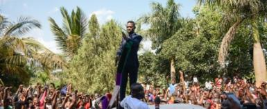 Kyagulanyi addressed cheering supporters outside his home as the police looked on.  By Isaac Kasamani (AFP)