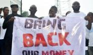 Liberians hold a banner during a demonstration over the disappearance of newly printed bills in September 2018, but the Central Bank of Liberia says the money never went missing.  By Zoom DOSSO (AFP/File)
