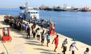 Migrants from Africa walk in line at a naval base in Tripoli after being rescued by Libyan coastguards in the Mediterranean Sea off the Libyan coast on August 29, 2017.  By MAHMUD TURKIA (AFP/File)
