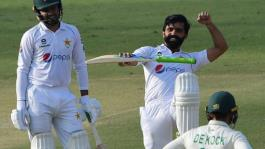 Pakistan's Fawad Alam celebrates after reaching his century while teammate Faheem Ashraf looks on.  By Asif HASSAN (AFP)