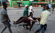 People rescue a wounded person after the triple bomb attack.  By ABDIRAZAK HUSSEIN FARAH (AFP)
