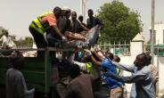 People unload from a truck to a morgue the bodies of victims in Bama, Borno State, northeastern Nigeria, on April 22, 2018, following twin suicide blasts inside of a mosque.  By AUDU MARTE (AFP)