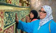 Pilgrims seek the blessing of Idriss I, a descendant of the Prophet Mohammed who founded Morocco's first Islamic dynasty, by placing a hand on his tomb or kissing it.  By FADEL SENNA (AFP)