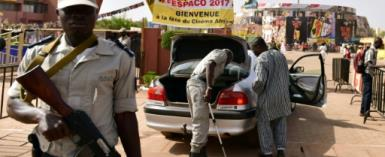 Police officers check cars at the entrance to the Pan-African Film and Television Festival (FESPACO) in Ouagadougou.  By ISSOUF SANOGO (AFP)