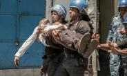 Police take away a plainclothes policeman injured in Monday's clashes.  By GIANLUIGI GUERCIA (AFP)