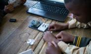 Pupils at the coding club in Ivory Park take wires from the breadboard -- the base for building an electronics circuit -- to a fan that they will programmme to work from a laptop.  By WIKUS DE WET (AFP)
