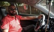 Ramez Wagih, an accountant in the morning and Uber driver in the afternoon, in his car in Cairo.  By MOHAMED EL-SHAHED (AFP)