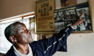 South African photojournalist Sam Nzima points to his photo illustrating the brutality of the apartheid regime, showing  Hector Pieterson carried by a fellow schoolboy after police gunned him down in Soweto in 1976.  By GIANLUIGI GUERCIA (AFP/File)