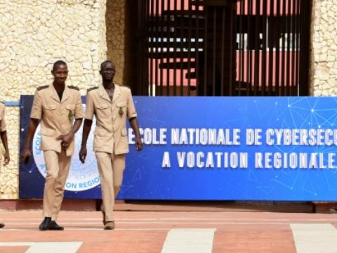 Students of the National School of Administration walk near the banner announcing the creation of a National School of Cybersecurity in Dakar on November 6, 2018.  By SEYLLOU (AFP)