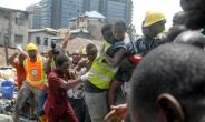 Survivor: Emergency workers pluck a child from the collapsed building. The disaster left 20 dead, according to a new toll.  By SEGUN OGUNFEYITIMI (AFP)
