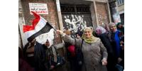 An Egyptian woman waves a national flag as she queues outside a polling centre to vote on a new constitution on January 14, 2014 in Mounira, a district of Cairo.  By Vriginie Nguyen Hoang (AFP)